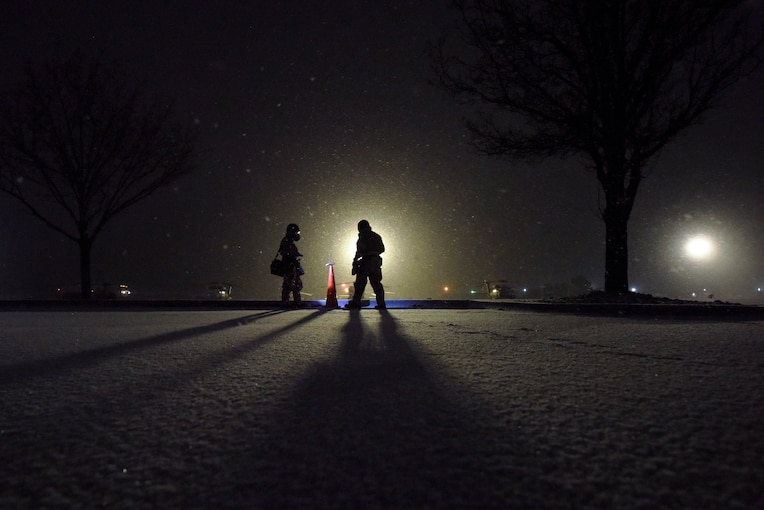 Airmen, shown in silhouette, stand in a snowy field at night.