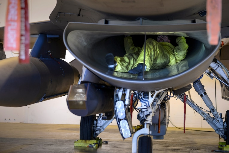 An airman conducts an inspection in a jet inlet.
