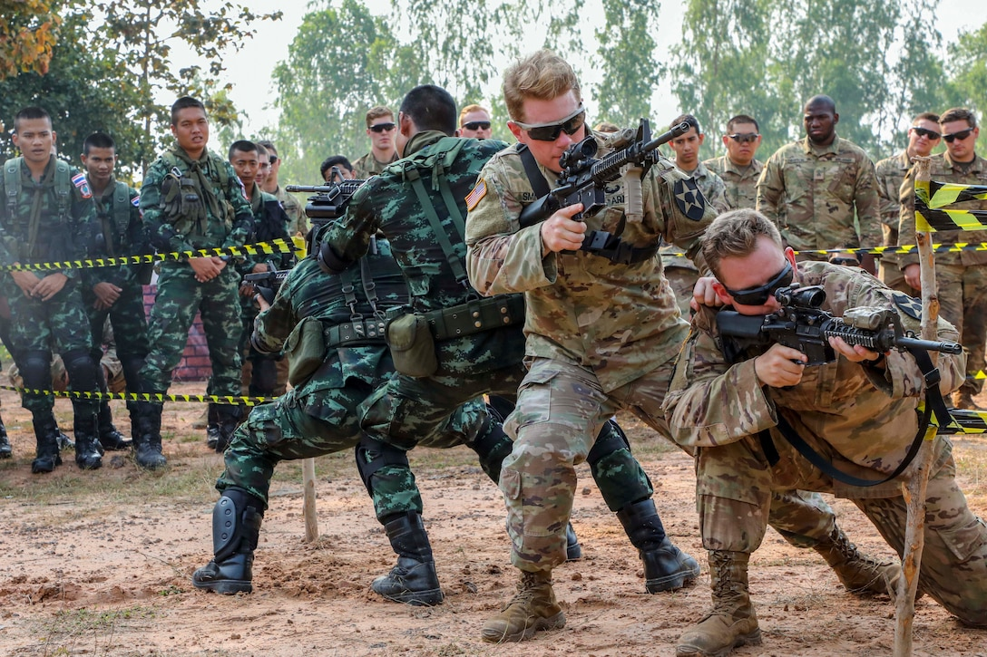 U.S. and Thai soldiers aim weapons in a cordoned-off outdoor area  as fellow troops watch.