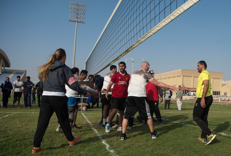 Qatar Emiri Air Force and U.S. Air Force members shake hands after finishing a volleyball match during Qatari National Sports Day Feb. 12, 2019, at Al Udeid Air Base, Qatar. U.S. and Qatar military forces were able to compete in team events including basketball, volleyball and soccer, as well as individual events such as swimming and ping pong throughout the morning. Qatari National Sports Day provided servicemembers from both nations an opportunity to strengthen military relations through friendly competition. (U.S. Air Force photo by Tech. Sgt. Christopher Hubenthal)