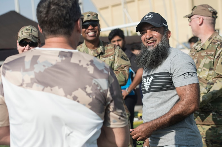 Brig. Gen. (Pilot) Saif Rashid Al-Khayarin, Qatar Emiri Air Force intelligence director (center right), talks with U.S. Air Force Brig. Gen Jason Armagost, 379th Air Expeditionary Wing commander (left), during Qatari National Sports Day Feb. 12, 2019, at Al Udeid Air Base, Qatar. U.S. and Qatar military forces were able to compete in team events including basketball, volleyball and soccer, as well as individual events such as swimming and ping pong throughout the morning. Qatari National Sports Day provided servicemembers from both nations an opportunity to strengthen military relations through friendly competition. (U.S. Air Force photo by Tech. Sgt. Christopher Hubenthal)