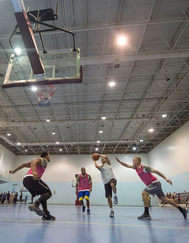 U.S. service members play a game of basketball during Qatari National Sports Day Feb. 12, 2019, at Al Udeid Air Base, Qatar. U.S. and Qatar military forces were able to compete in team events including basketball, volleyball and soccer, as well as individual events such as swimming and ping pong throughout the morning. Qatari National Sports Day provided servicemembers from both nations an opportunity to strengthen military relations through friendly competition. (U.S. Air Force photo by Tech. Sgt. Christopher Hubenthal)