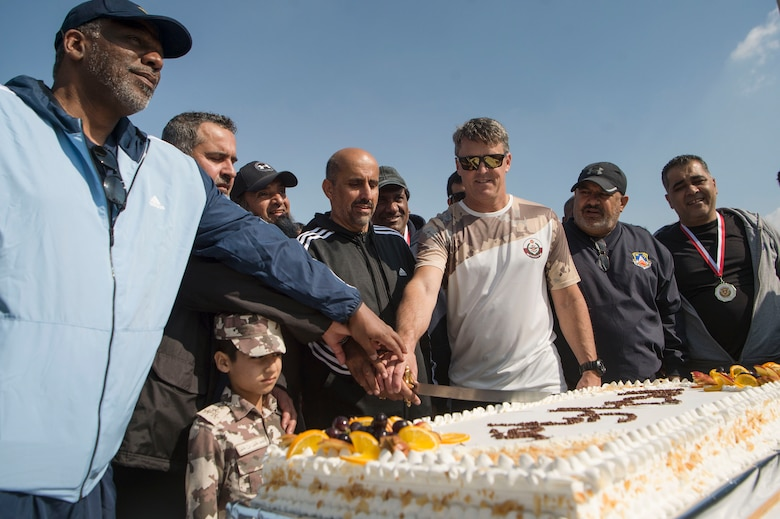 U.S. Air Force Brig. Gen Jason Armagost, 379th Air Expeditionary Wing commander, cuts a cake with Qatar Emiri Air Force leadership during Qatari National Sports Day Feb. 12, 2019, at Al Udeid Air Base, Qatar. U.S. and Qatar military forces were able to compete in team events including basketball, volleyball and soccer, as well as individual events such as swimming and ping pong throughout the morning. Qatari National Sports Day provided servicemembers from both nations an opportunity to strengthen military relations through friendly competition. (U.S. Air Force photo by Tech. Sgt. Christopher Hubenthal)