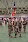 Regimental Command Sgt. Maj. Douglas Galick receives the regimental colors from Brig. Gen. Robert Whittle Jr., USAES commandant, during a ceremony held Friday in Nutter Field House. (Photo Credit: Maj. Dustin Berry)