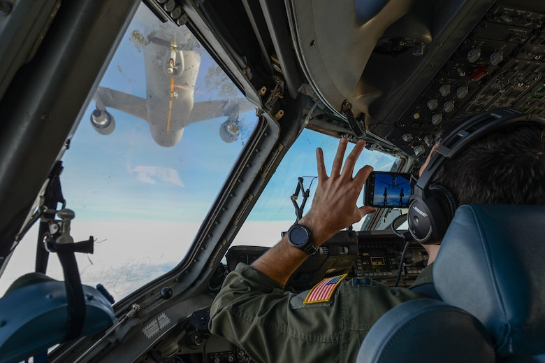 A pilot documents training while another pilot prepares to refuel from a KC-46 Pegasus