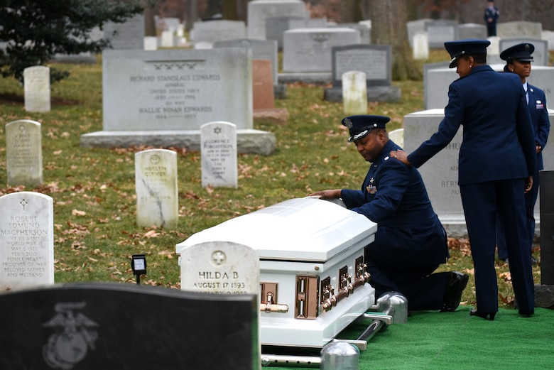 U.S. Air Force Maj. Gen. (Ret.) Marcelite Harris' son Lt. Col. Steven Harris kneels at his mother's gravesite after her full honors funeral