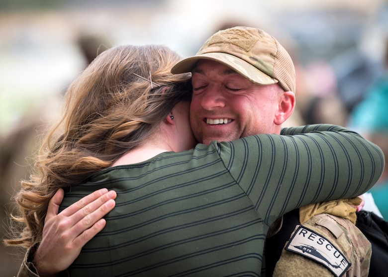 An Airman embraces his spouse during a redeployment ceremony