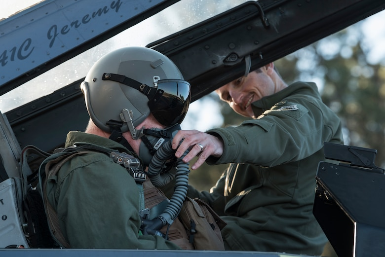 A pilot helps another pilot with his oxygen mask
