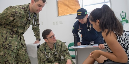 Lt. John Sullivan, Lt. Cmdr. Robert Lennon, and Brazilian Navy Lt. Gilvan Martins examine a patient during a visit to the Heraclio Emiliano Moda medical clinic in Axinim, Brazil, Feb. 6.