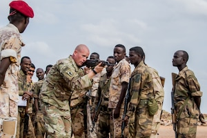 An American soldier instructs Djiboutian soldiers.