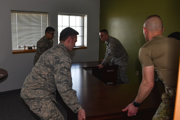 Airmen with the 90th Maintenance Group move a desk in a newly renovated office, Feb. 4, 2019, on F.E. Warren Air Force Base, Wyo. The 90th Missile Maintenance Squadron was selected as one of the recipients of the innovation funds from the Warren Shootout. The squadron recently renovated six storage closets and turned them into functioning offices. (U.S. Air Force photo by Airman 1st Class Braydon Williams)