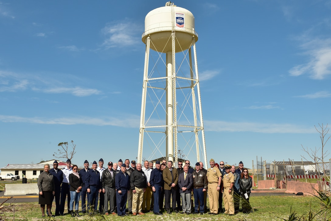 Members of the Great American Defense Community and Tyndall Air Force Base pose for a group photo during the unveiling of a logo on the installation's water tower at Tyndall Air Force Base, Fla., Feb. 13, 2019. Tyndall was awarded the Great American Defense Community Award for 2019 with a commemorative logo painted on the water tower to represent Bay County's accomplishments. Bay County is one of five communities across the country to be named a Great American Defense Community in 2019.  (U.S. Air Force photo by Staff Sgt. Alexandre Montes)