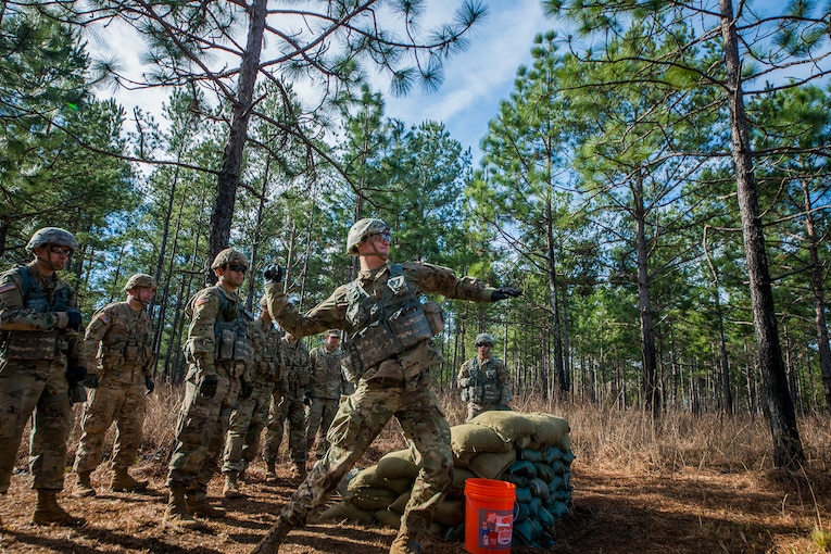 Soldiers train in the woods.