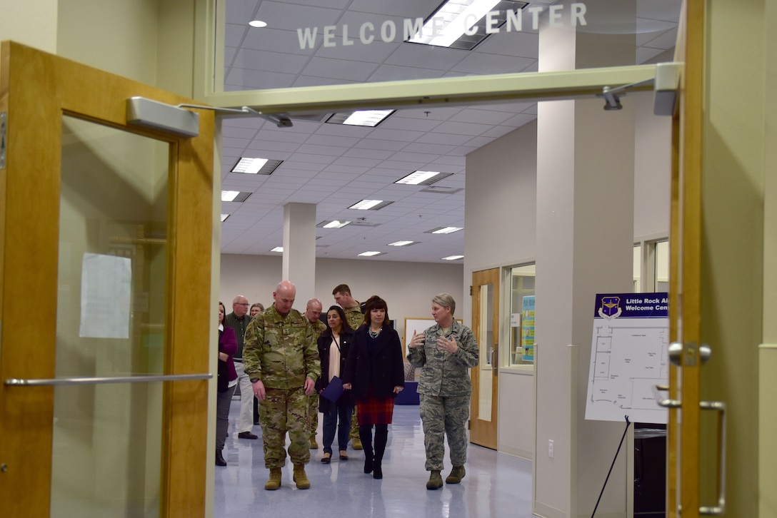 A woman in the Airman Battle Uniform shows people a welcome center.