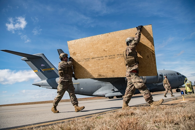 Airmen from the 621st Contingency Response Squadron offload plywood from a C-17 Globemaster III during Exercise Crescent Moon Feb. 12, 2019, at North Auxiliary Airfield in North, S.C.