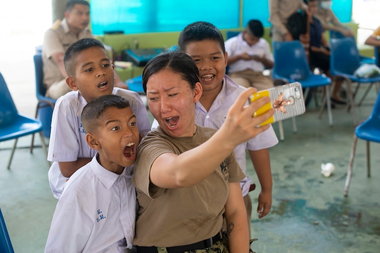 A sailor takes a selfie with three children.