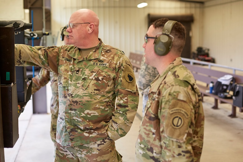 Lt. Col. Patrick Sleem instructs Sgt. 1st Class B.O. Combs on stance and body position during Service Pistol Team training.