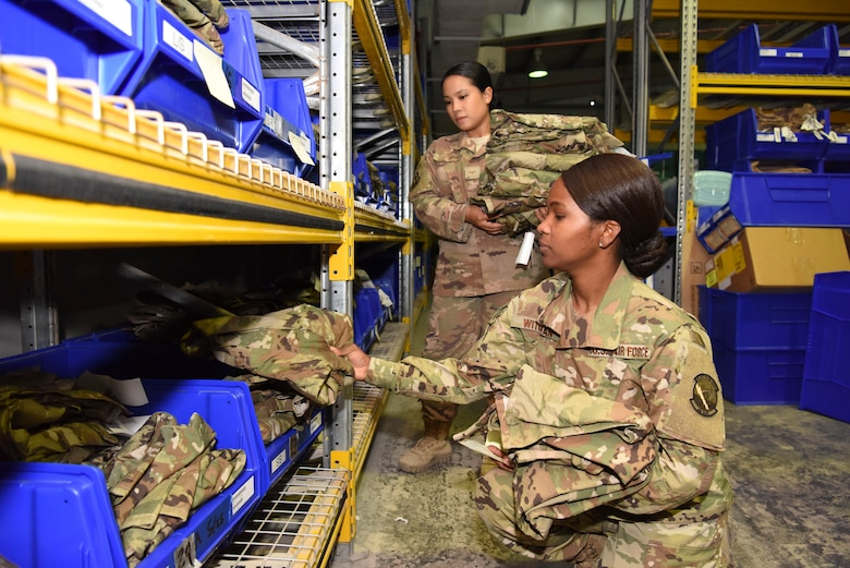 Senior Airman Kerby Witman, 380th ELRS customer service technician (front), and Airman 1st Class Michelle Gutierrez, 380th ELRS customer service technician, perform a uniform inspection inside of Desert Depot at Al Dhafra Air Base, United Arab Emirates, Feb. 11, 2019.