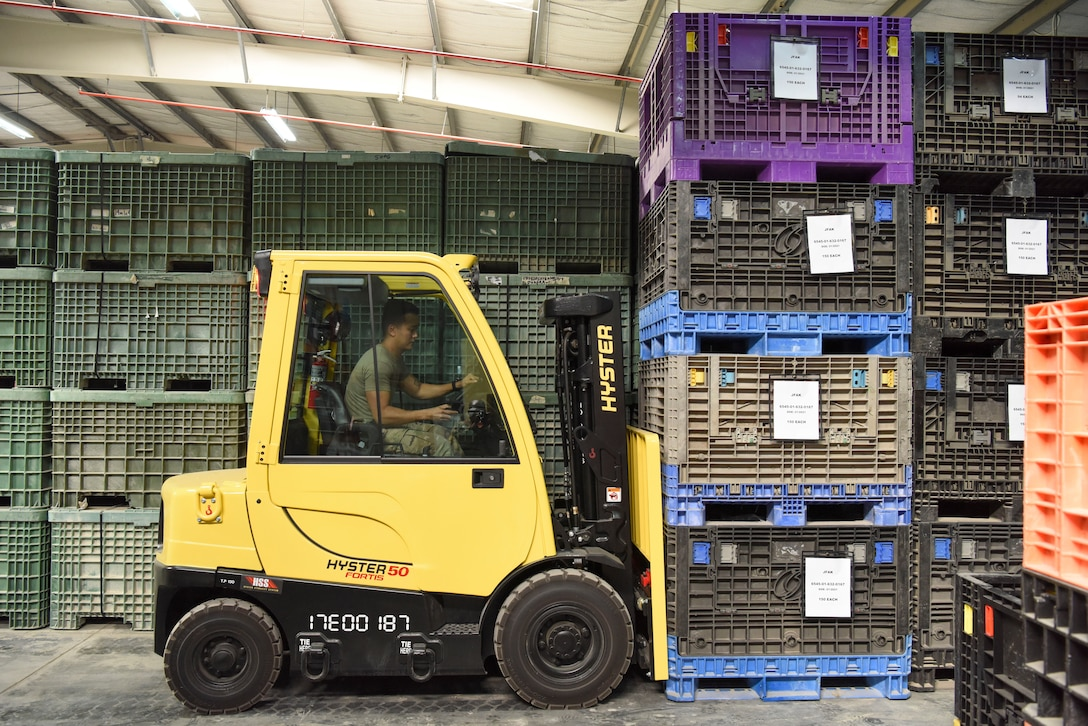 Tech. Sgt. Caresia Baldwin, 380th Expeditionary Staff Sgt. Karl Santos, 380th Expeditionary Logistics Readiness Squadron IPE supervisor, uses a forklift to reorganize containers in the equipment accountability office at Al Dhafra Air Base, United Arab Emirates, Feb. 11, 2019.