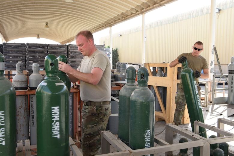 Staff Sgt. Tanner Collins, 380th Expeditionary Logistics Readiness Squadron inventory NCOIC, and Staff Sgt. Cody Sharkey, 380th ELRS hazardous materials section chief, store compressed cylinders at Al Dhafra Air Base, United Arab Emirates, Feb. 11, 2019.