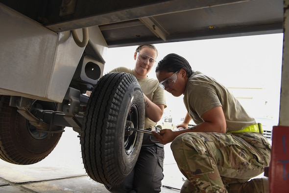 Airman 1st Class Sarah Derringer, 380th Expeditionary Maintenance Squadron Aerospace Ground Equipment technician, holds a tire in place while Airman 1st Class Mia Duran, 380th Maintenance Squadron Aerospace Ground Equipment technician, fastens the tire's bolts Feb. 11, 2019, at Al Dhafra Air Base, United Arab Emirates.