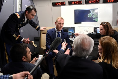 Acting Defense Secretary Patrick M. Shanahan talks to reporters on the flight home from Munich, Germany
