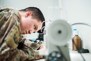 U.S. Air Force Staff Sgt. Andrew Yabumoto, 493rd EFS aircrew flight equipment apprentice, sews a harness February 14, 2019 in Southwest Asia. The AFE shop works around the clock to ensure aircrew members' daily equipment, which includes G-suits, night vision goggles, harnesses, helmets and oxygen masks are ready to go at a moment's notice. (U.S. Air Force photo by Staff Sgt. Delano)