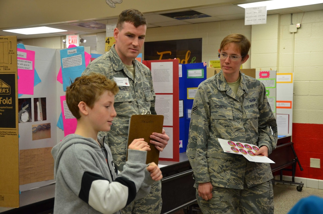 Elijah Norsworthy, a 5th grader at Croton Elementary School in Melbourne, Fla., explains his scientific method to  Staff Sgt. Samuel Carmichael and Airman 1st Class Cynthia A. Schroll, members of the Air Force Technical Applications Center.  The Airmen served as judges for the school's annual science fair Feb. 7, 2019.   (U.S. Air Force photo by Susan A. Romano)