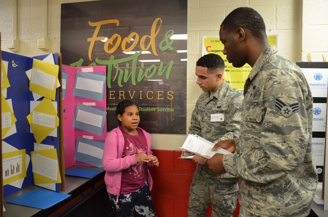 Jarvienis Rosario, a 4th grader at Croton Elementary School, answers questions from Science Fair judges Senior Airman Harold Fisher Jr., and Airman 1st Class Ruben Vera-Colon who traveled from Patrick AFB, Fla., to Croton Feb. 7, 2019 to assist the school with its annual event.  Fisher and Vera-Colon are members of the Air Force Technical Applications Center, the Department of Defense's sole nuclear treaty monitoring center.  (U.S. Air Force photo by Susan A. Romano)