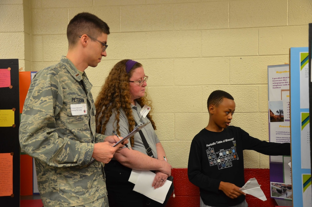 2nd Lt. Tyler Peterson and Claudia Granger, scientists from the Air Force Technical Applications Center at Patrick AFB, Fla., listen to Bryce Jeffrey, a 6th grader at Croton Elementary School, describe his science fair project that dealt with the aerodynamics of paper airplanes.  The AFTAC duo was part of a team of 18 Airmen – military and civilian alike – who volunteered to serve as science fair judges Feb. 7, 2019.  (U.S. Air Force photo by Susan A. Romano)