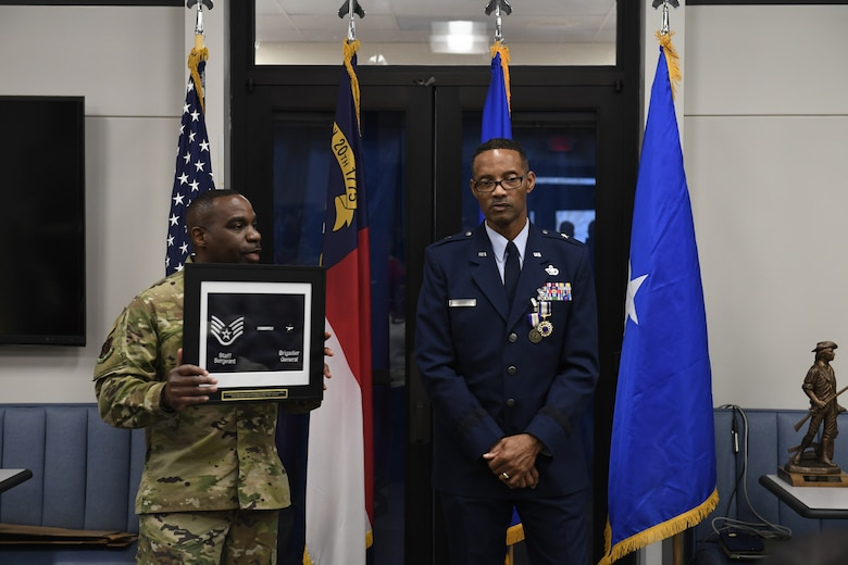 U.S. Air Force Chief Master Sgt. Maurice L. Williams, Senior Enlisted Leader for the Kansas National Guard, holds a plaque showing Brig. Gen. Clarence Ervin's highest rank as an enlisted member and as a general officer during the retirement reception at the North Carolina Air National Guard Base (NCANG), Charlotte Douglas International Airport, Feb. 09, 2019. Family, friends and guard members gathered to celebrate the retirement of Gen. Ervin, Chief of Staff for the NCANG, after serving in the military for 37 years.