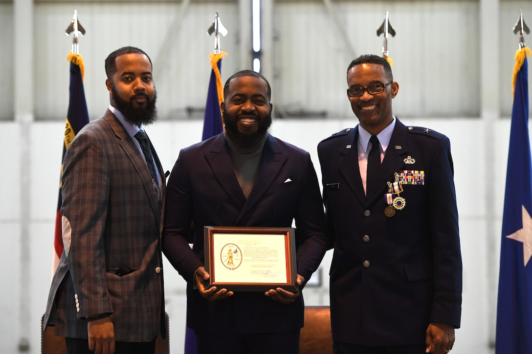 U.S. Air Force Brig. Gen. Clarence Ervin (right) and his two sons, CJ (left) and Chris (center), accept an award on behalf of their late mother and Gen. Ervin's late wife during his retirement ceremony at the North Carolina Air National Guard Base (NCANG), Charlotte Douglas International Airport, Feb. 09, 2019. Family, friends and guard members gathered to celebrate the retirement of Gen. Ervin, Chief of Staff for the NCANG, after serving in the military for 37 years.
