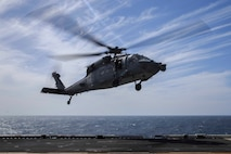 An MH-60S Seahawk, carrying cargo, prepares to land on the flight deck of the Wasp-class amphibious assault ship USS Kearsarge. Aircraft routinely transport 22nd Marine Expeditionary Unit personnel, mail and cargo to the Kearsarge. Marines and Sailors with the 22nd MEU and Kearsarge Amphibious Ready Group are deployed to the 5th Fleet area of operations in support of naval operations to ensure maritime stability and security in the Central Region, connecting the Mediterranean and the Pacific through the western Indian Ocean and three strategic choke points. (U.S. Marine Corps photo by Lance Cpl. Tawanya Norwood)