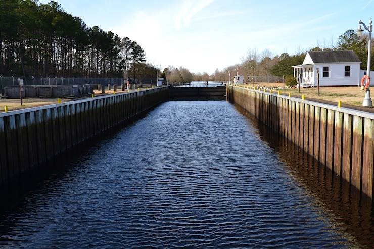 A view of the Deep Creek Lock, a waterway with wooden planks on the sides and a small house on the right side. the left side has trees