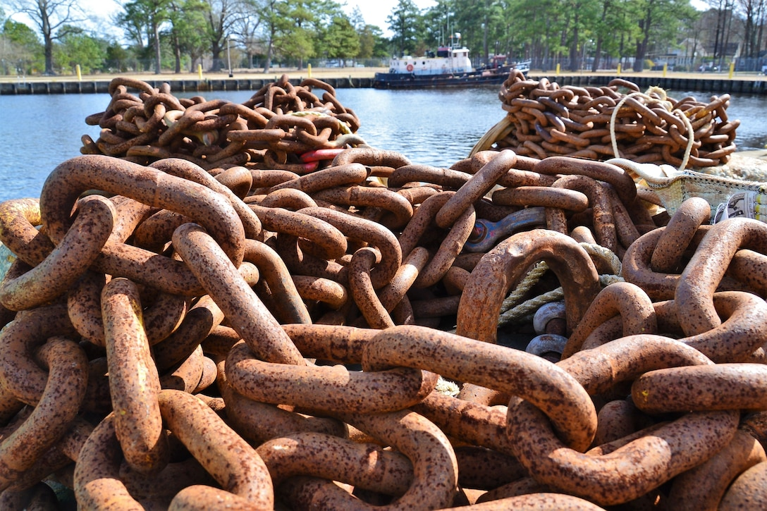 A pile of rusted chain is in the foreground and in the background is a moored boat.
