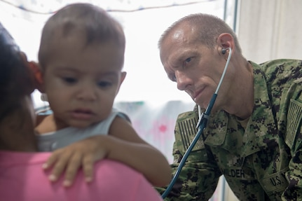 Cmdr. Edmund Milder examines a young patient at the Benjamin Silva-Calama clinic in Calama, Brazil, Feb. 14.