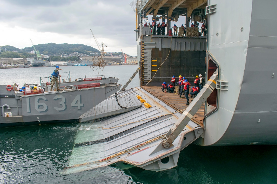 Sailors connect a landing craft to the open ramp of a ship in water.
