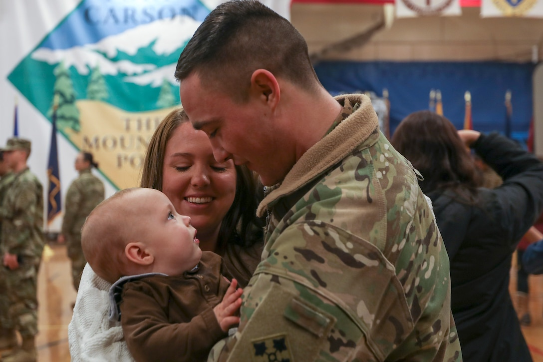Soldier in camouflage uniform reunites with family.