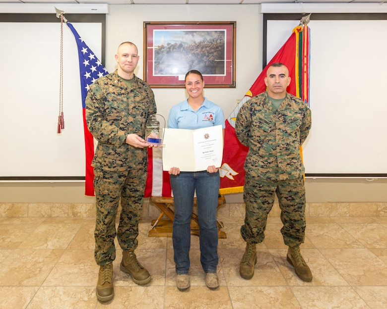 Sergeant Emily Rowe, stableman, was awarded Noncommissioned Officer of the Year by Col. Craig Clemans, Base Commander, and Sgt. Maj. Sergio MartinezRuiz, Base Sergeant Major, during the quarterly awards breakfast aboard Marine Corps Logistics Base Barstow, Calif., Jan. 29. (U.S. Marine Corps Photo by Jack J. Adamyk)