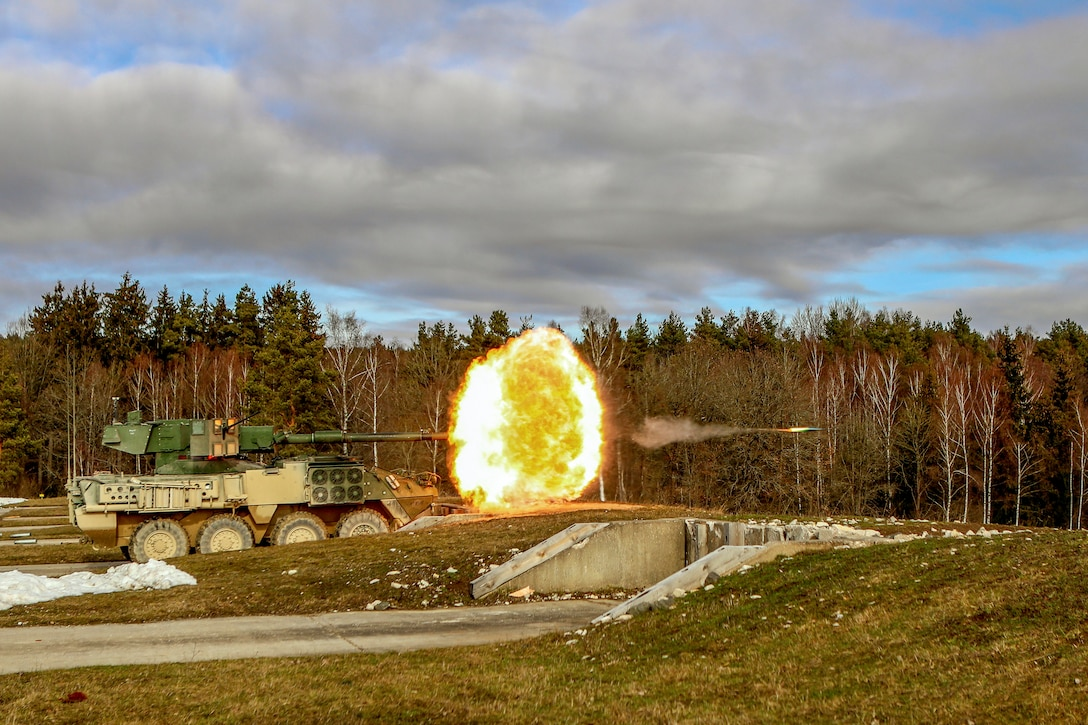 A projectile and a fireball shoot out from a military vehicle's gun.