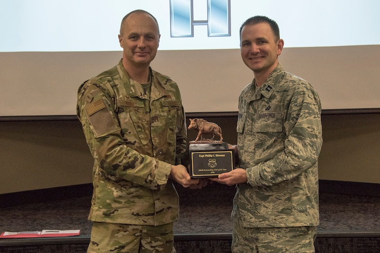 Col. Robert I. Kinney, 188th Wing commander, presents Capt. Phillip J. Stevens, the 188th Wing Outstanding Company Grade Officer of the Year, with a trophy at a commander's call held at Ebbing Air National Guard Base, Ark., Jan. 13, 2019. (U.S. Air National Guard photo by Tech. Sgt. John E. Hillier)