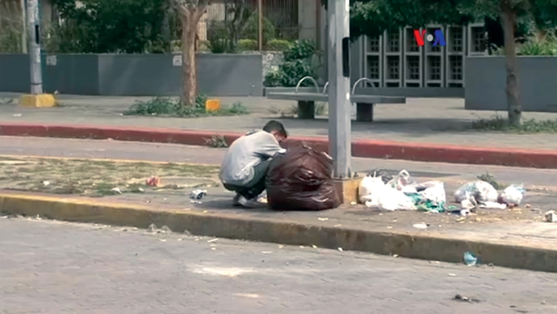 A Venezuelan eating from a garbage bag due to food shortages in 2017. (VOA) 