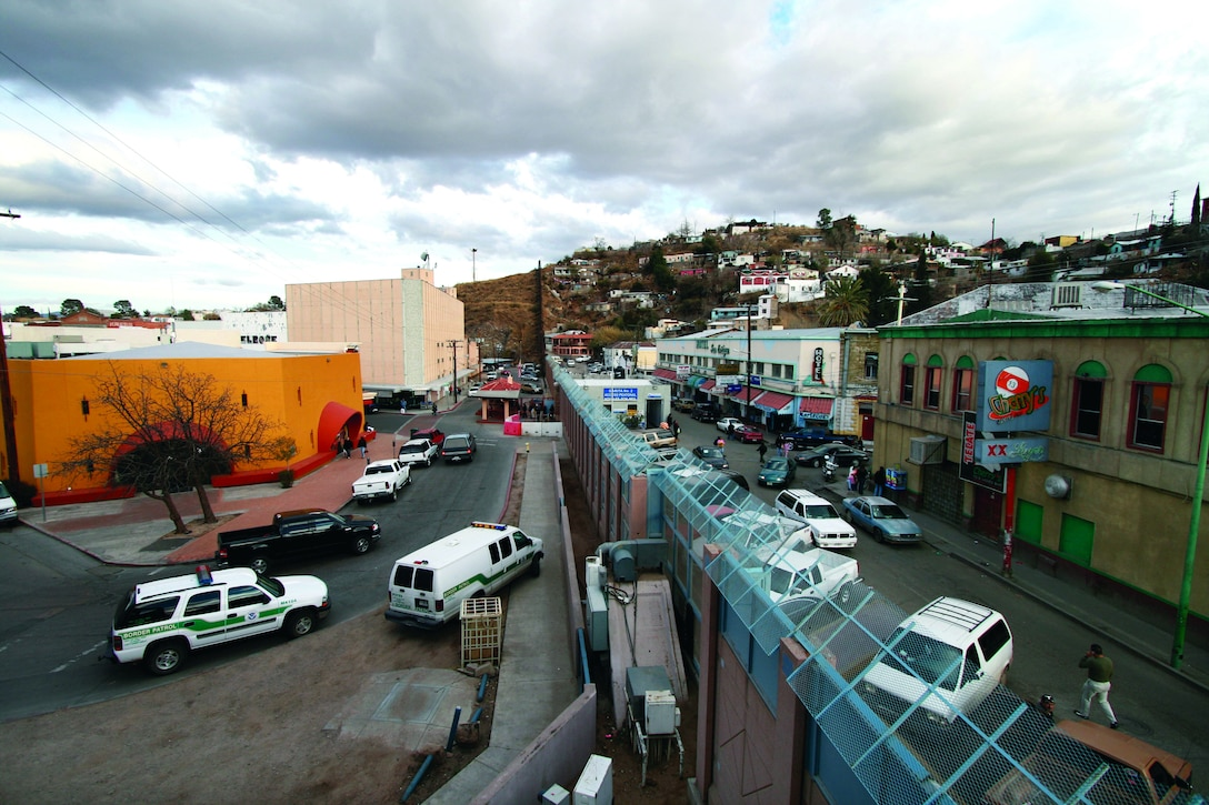 The towns of Nogales, Ariz., left, and Nogales, Mexico, stand separated by a high concrete and steel fence, Thursday, Jan. 18, 2007. Many consider the area one of the most dangerous along the border with numerous reports from U.S. Border Patrol agents of being spit on, having rocks thrown at them, and gunfire. Despite the existence of a legal crossing point, enough illegal crossings occur to warrant 24-hour Border Patrol operations there. (U.S. Army photo by Sgt. 1st Class Gordon Hyde) (Released)