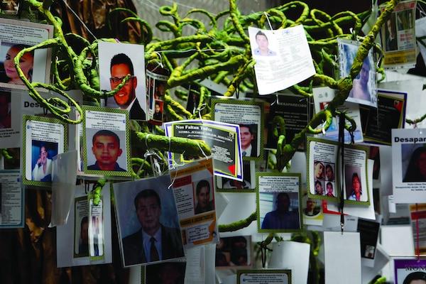 Fotografías de personas desaparecidas cuelgan de un árbol de la vida durante una ceremonia en el Día Internacional de las Víctimas de Desapariciones Forzadas en la Cámara de Diputados de México, en la Ciudad de México, México, Agosto 30, 2017. La Comisión Interamericana de Derechos Humanos (CIDH) realiza su tercera visita a México para dar seguimiento al Caso de los 43 estudiantes desaparecidos en septiembre 26 de 2014. (Ginnette Riquelme para CIDHTransferred from Flickr2Commons to Wikimedia by Warko. Licensed under Creative Commons Attribution 2.0 Generic License. Photo unaltered.