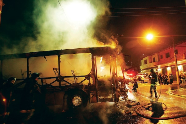 Firefighters fighting a fire in one of the 90 buses destroyed in a series of attacks coordinated by the PCC in São Paulo in May 2006. (Folhapress)