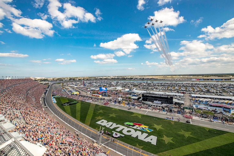 Jets fly in formation over a crowd at the Daytona International Speedway.