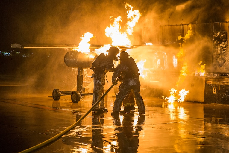 A service member fights a fire.
