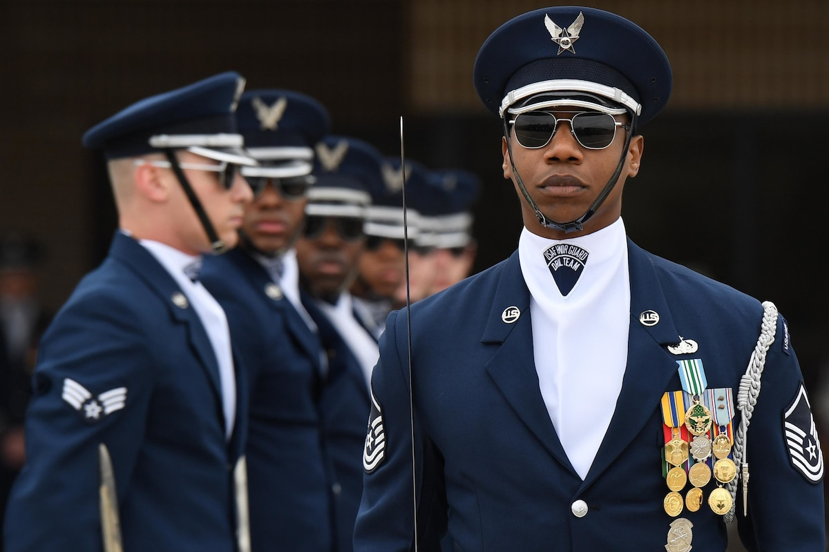 An airman stands in front of line of airmen during a performance.