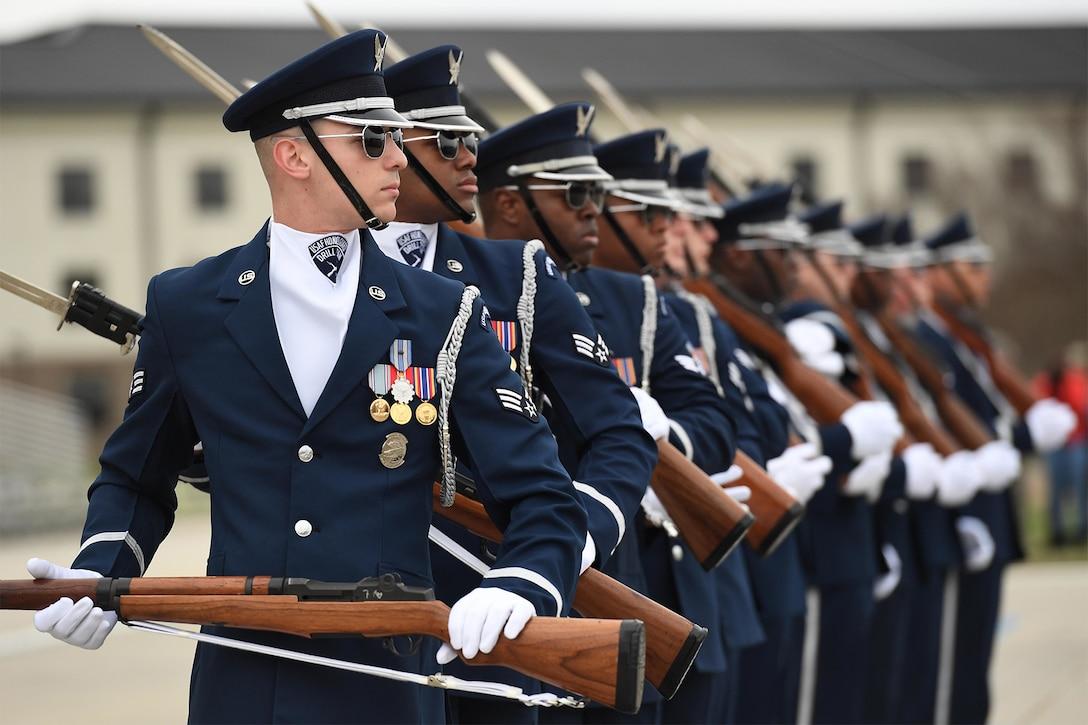Service members participate in a honor guard routine.