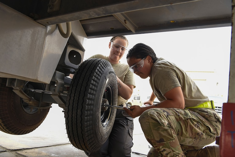 Service members change a tire.